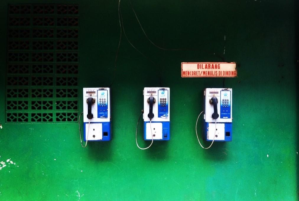 Blue Pay Phone On Green Wall. Photo Credit Muchlis Akbar / EyeEm via Getty Images